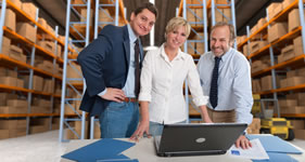Three people in front of laptop in warehouse